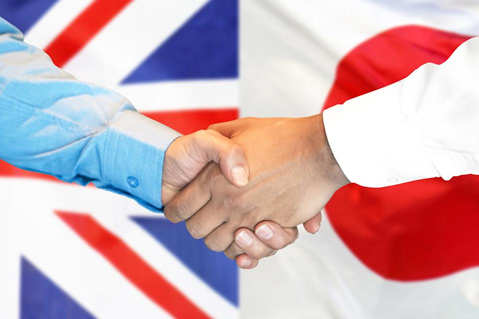 Business handshake on the background of two flags. Men handshake on the background of the United Kingdom and Japan flag. Support concept
