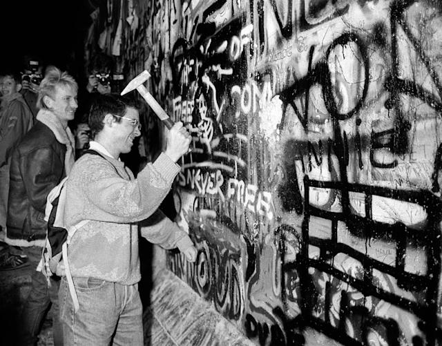 A man hammers a section of the Berlin Wall near the Brandenburg Gate after the opening of the East German border was announced on Nov. 9, 1989. (Photo: Fabrizio Bensch/Reuters)