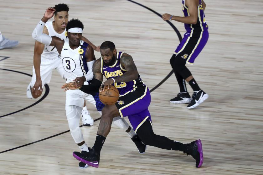 Los Angeles Lakers forward LeBron James (23) drives to the basket against Indiana Pacers guard Aaron Holiday (3) during the fourth quarter of an NBA basketball game Saturday, Aug. 8, 2020, in Lake Buena Vista, Fla. (Kim Klement/Pool Photo via AP)