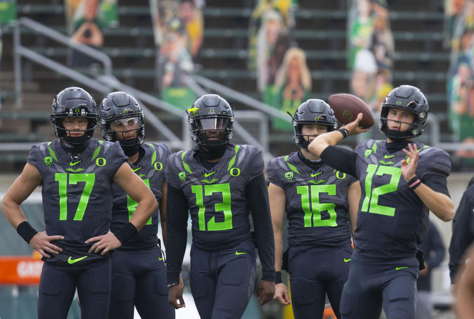 Oregon backup quarterbacks from left, Cale Millen, Robby Ashford, Anthony Brown and Bradley Yaffe watch as starting quarterback Tyler Shough warms up before an NCAA college football game against UCLA Saturday, Nov. 21, 2020, in Eugene, Ore. (AP Photo/Chris Pietsch)