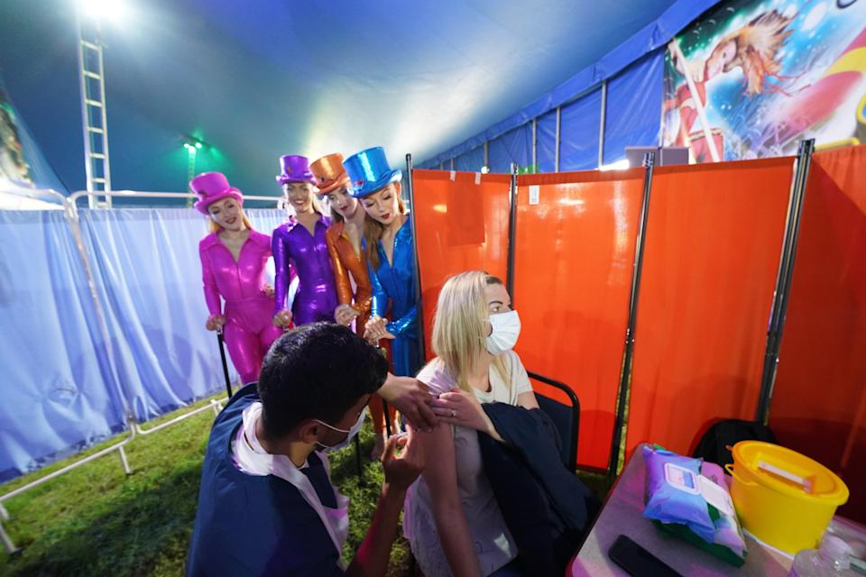 Performers from Circus Extreme watch as Rhiannon Alexander, 34, from Bradford, receives a Covid-19 vaccination at a pop-up clinic in a marquee in Halifax (Owen Humphreys/PA) (PA Wire)