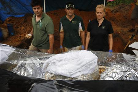 Volunteer Brett Harding (L), University of South Florida associate professor Chistian Wells, and assistant professor Erin Kimmerle (R) look at a body bag containing remains removed from an unmarked grave at the now closed Arthur G. Dozier School for Boys in Marianna, Florida, September 2, 2013. REUTERS/Edmund D. Fountain/Pool