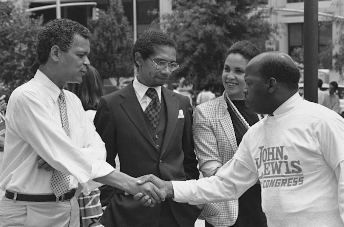 State Sen. Julian Bond greets Atlanta City Councilman John Lewis, right, during an election rally in downtown Atlanta, Monday, August 11, 1986 as former state Rep. Bobby Hill, center, looks on. Bond and Lewis are running for the U.S. 5th Congressional District seat vacated by Wyche Fowler, and Hill is running for Lt. Governor. (Photo: Ric Feld/AP)