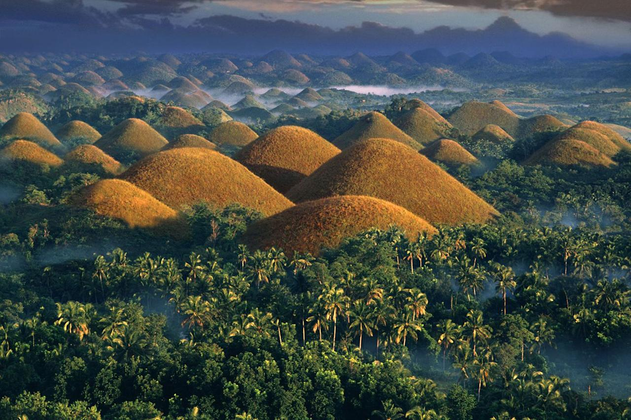 <p>A morning fog covers the land near the Chocolate Hills in the Bohol province of the Philippines // Date unknown</p>