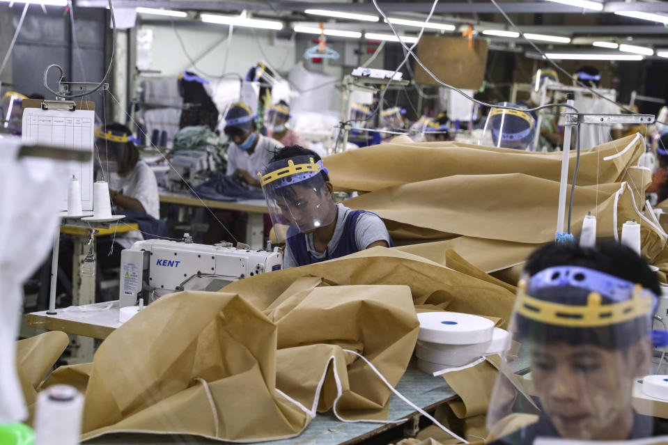 Workers wearing face mask and face shield to help curb the spread of the new coronavirus, sew surgical gown as they work at a garment factory Thursday, May 28, 2020, at Industrial Zone in Yangon, Myanmar. Despite a poor public health infrastructure and crowded urban areas, Myanmar has reported a surprising low number of COVID-19 cases, with just a little over 200 confirmed and a few deaths. (AP Photo/Thein Zaw)