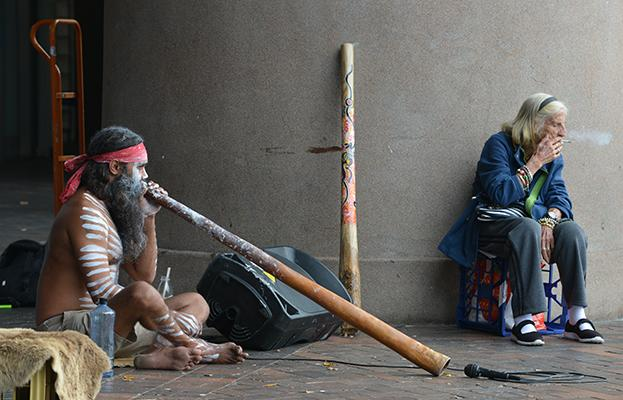 An elderly woman smokes a cigarette while an Aboriginal man plays a didgeridoo in Circular Quay in Sydney on April 4, 2017.