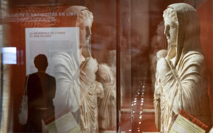Antique figures on display behind glass.