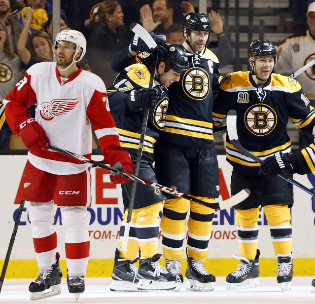 Detroit Red Wings' Drew Miller skates away as Boston Bruins' Jarome Iginla, right, Milan Lucic (17) and Zdeno Chara celebrate after Chara scored during the third period of Boston's 4-1 win in Game 2 of a first-round NHL hockey playoff series in Boston Sunday, April 20, 2014. (AP Photo/Winslow Townson)