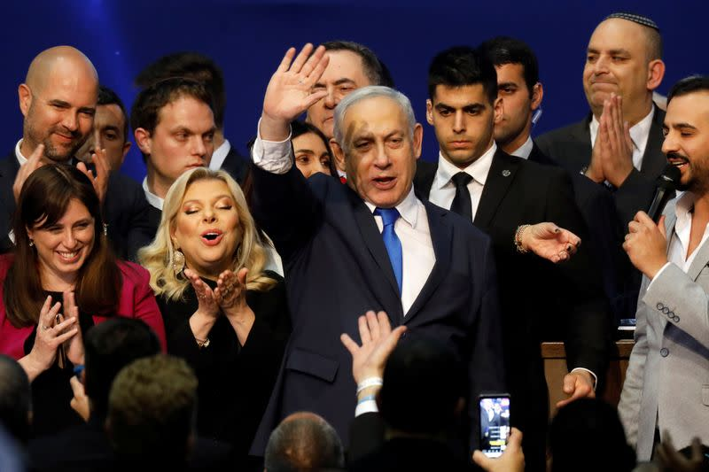 Israeli Prime Minister Benjamin Netanyahu stands next to his wife Sara as he waves to supporters following the announcement of exit polls in Israel's election at his Likud party headquarters in Tel Aviv