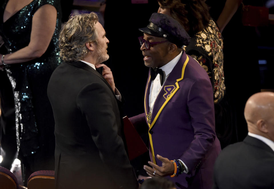Joaquin Phoenix, left, speaks with Spike Lee in the audience at the Oscars on Sunday, Feb. 9, 2020, at the Dolby Theatre in Los Angeles. (AP Photo/Chris Pizzello)