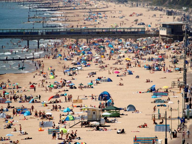 Sunbathers enoy the warm weather on the beach near Boscombe Pier in Bournemouth: Photo by ADRIAN DENNIS/AFP via Getty Images