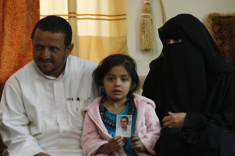 In this photo taken on Friday, Feb. 14, 2014, Afnan, 6, holds a picture of her father Bandar al-Hassani, who was killed in a US drone strike last year sits betwee her grandparents Omar al-Hassani, and Khadija Hassan. Beside Bandar, al-Hassanis lost two more sons, one in another US drone strike in 2013 and third during fighting between al-Qaida militants and government forces in 2012. (AP Photo/Hani Mohammed)