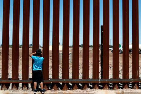 A child looks through the border wall during the visit of U.S. President Donald Trump to Calexico, California, as seen in Mexicali, Mexico April 5, 2019. REUTERS/Carlos Jasso/Files