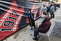 Marcel Murad, sitting, and his wife Elen, left, wait in line to vote at Fenway Park, Saturday, Oct. 17, 2020, in Boston. (AP Photo/Michael Dwyer)