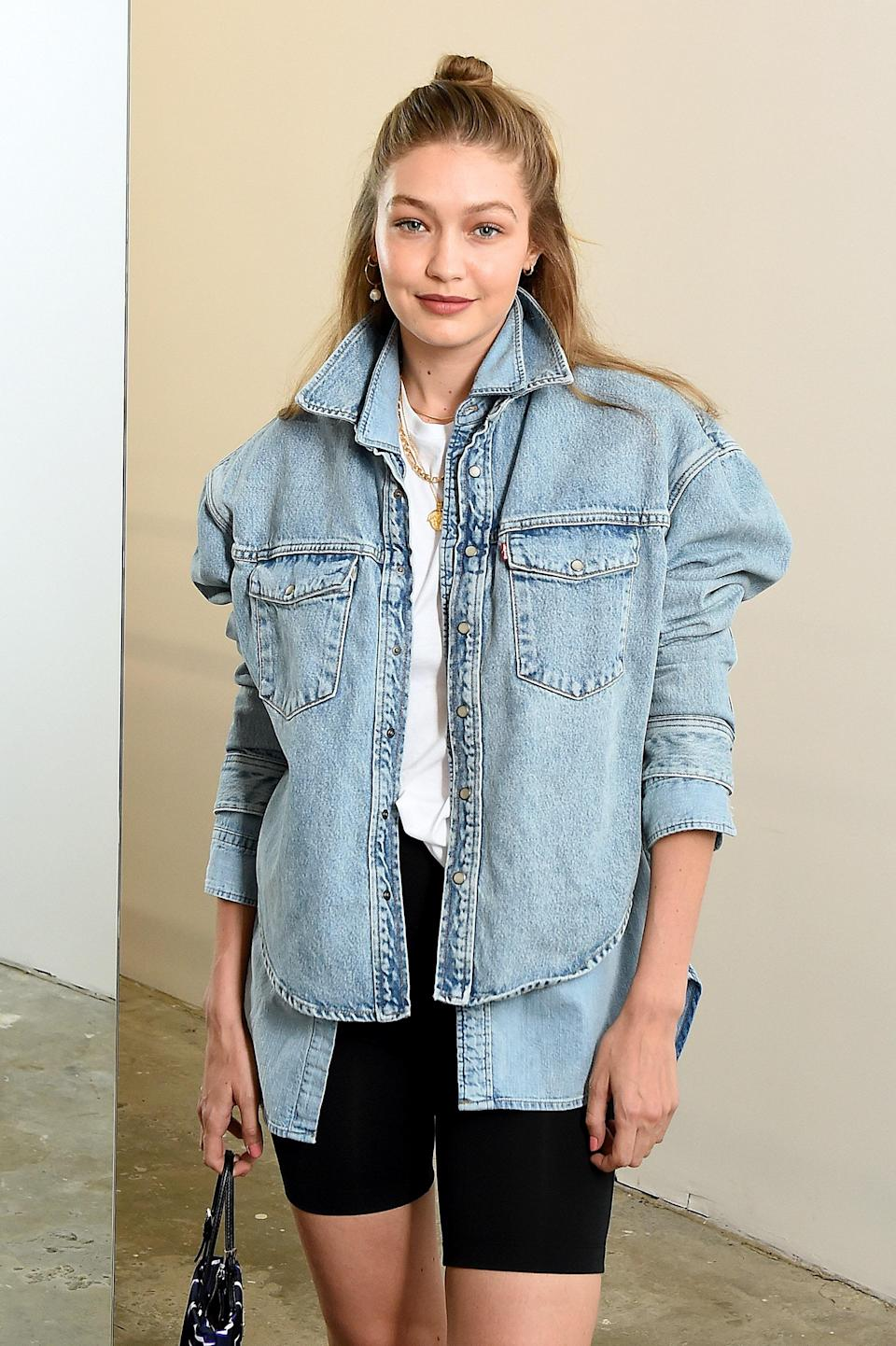 The '90s are calling! Gigi rocks one of the decade's best model-off-duty looks: a plain white tee, black bike shorts, and a denim jacket. Not just any denim jacket; this seems to be two chambray button-downs pulling double duty and serving MAJOR shoulders. What can we say? She loves her denim!