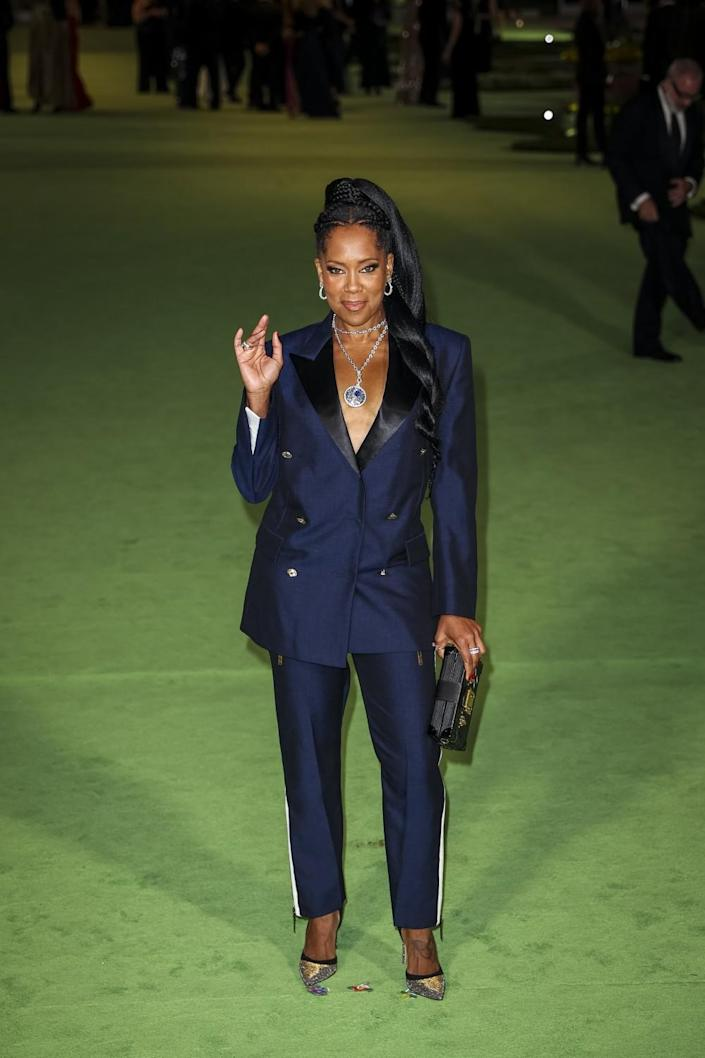 A woman in a navy blue suit posing on a green carpet