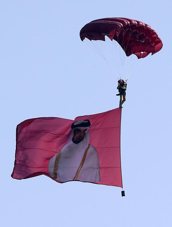 A paraglider, with a flag with an image of Qatar's Emir Sheikh Tamim bin Hamad, flies over the capital during National Day celebrations in Doha