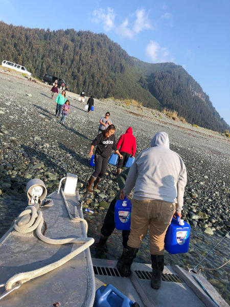 This Aug. 29, 2019, photo provided by Katrina Berestoff shows residents of Nanwalek, Alaska, filling up water jugs in the nearby Kenai Peninsula community of Port Graham. Alaska's hot, dry summer has led to extreme measures for severe drought conditions for the Native communities of Nanwalek and Seldovia, prompting regional officials to declare a disaster declaration. (Katrina Berestoff via AP)
