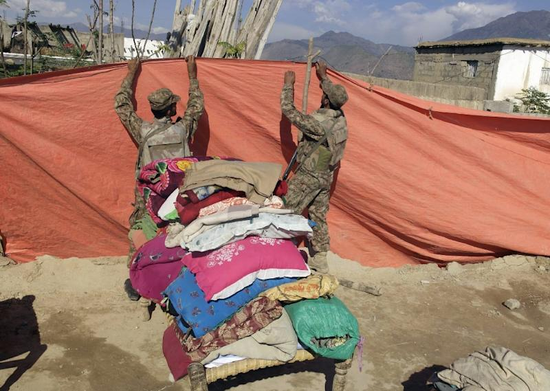Pakistani soldiers arrange a temporary tent for displaced people at the quake-hit area of Lower Dir on October 27, 2015 (AFP Photo/Ehsan Ullah)