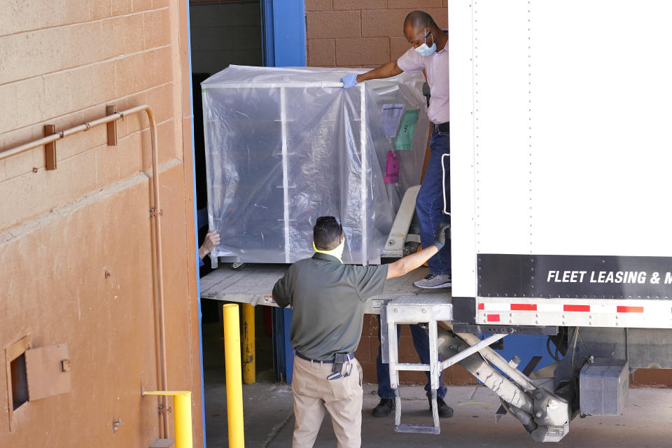 FILE - In this April 21, 2021 file photo, officials unload election equipment into the Veterans Memorial Coliseum at the state fairgrounds in Phoenix. Arizona's largest county has approved nearly $3 million for new vote-counting machines to replace those given to legislative Republicans for a partisan review of the 2020 election. The GOP-controlled Maricopa County Board of Supervisors said Wednesday, July 14, 2021 that the machines were compromised because they were in the control of firms not accredited to handle election equipment. (AP Photo/Matt York, File)