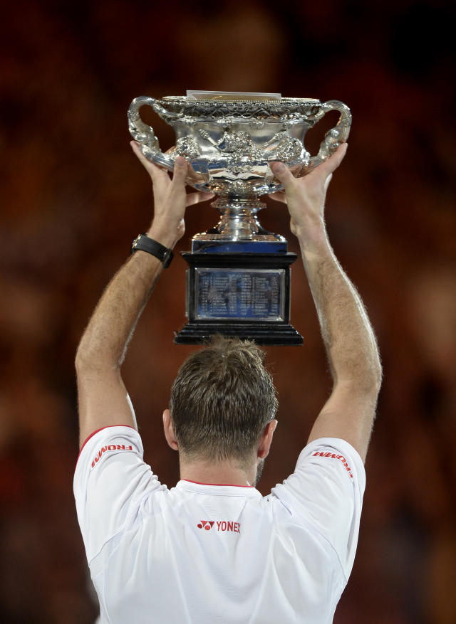 Stanislas Wawrinka of Switzerland holds up the trophy after defeating Rafael Nadal of Spain in the men's singles final at the Australian Open tennis championship in Melbourne, Australia, Sunday, Jan. 26, 2014. (AP Photo/Andrew Brownbill)