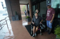 With flood water running through the streets people move outside a hotel for a view, Wednesday, Sept. 16, 2020, in Pensacola, Fla. Hurricane Sally made landfall Wednesday near Gulf Shores, Alabama, as a Category 2 storm, pushing a surge of ocean water onto the coast and dumping torrential rain that forecasters said would cause dangerous flooding from the Florida Panhandle to Mississippi and well inland in the days ahead.(AP Photo/Gerald Herbert)