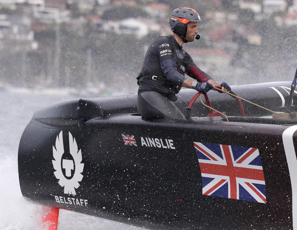 FILE - In this Feb. 29, 2020, file photo, skipper Ben Ainslie steers the boat as the British team slows after crossing the finish line in the second fleet race of the SailGP series in Sydney. Britain beat Australia in the final match race. The second regatta in SailGP's second season will be notable for who's missing as much as who will be sailing in Taranto, Italy.The biggest absence will be that of Ainslie, who helmed the British team to victory in the podium race in the opening regatta in Bermuda after Tom Slingsby's defending champion Australian team dominated the fleet racing. (AP Photo/Rick Rycroft, File)