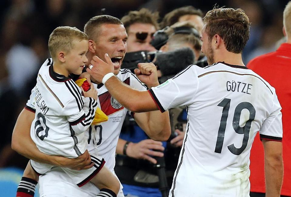 Germany's Lukas Podolski holds is son as he celebrates with Mario Goetze, right, after the World Cup final soccer match between Germany and Argentina at the Maracana Stadium in Rio de Janeiro, Brazil, Sunday, July 13, 2014. Germany beat Argentina 1-0 to win the World Cup. (AP Photo/Frank Augstein)