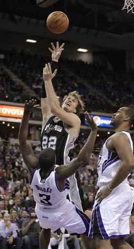 San Antonio Spurs forward Tiago Splitter, center, of Brazil, charges into Sacramento Kings guard Aaron Brooks as Kings forward Chuck Hayes, right, looks on during the first quarter of an NBA basketball game in Sacramento, Calif., Friday, Nov. 9, 2012. (AP Photo/Rich Pedroncelli)