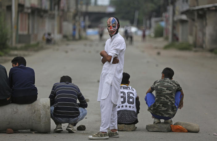 A Kashmiri wears a mask and waits with others during a protest against the Indian government in Srinagar, India, Friday, Aug. 9, 2019. The predominantly Muslim area has been under an unprecedented security lockdown and near-total communications blackout to prevent unrest and protests after India's Hindu nationalist-led government said Monday it was revoking Kashmir's special constitutional status and downgrading its statehood. (AP Photo/Altaf Qadri)