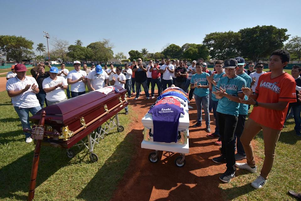 Relatives stand by the coffins of shooting victims in Minatitlan