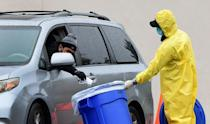 A driver drops his COVID-19 test into a bin at a coronavirus mobile testing site in Los Angeles on April 10, 2020 (AFP Photo/Frederic J. BROWN)