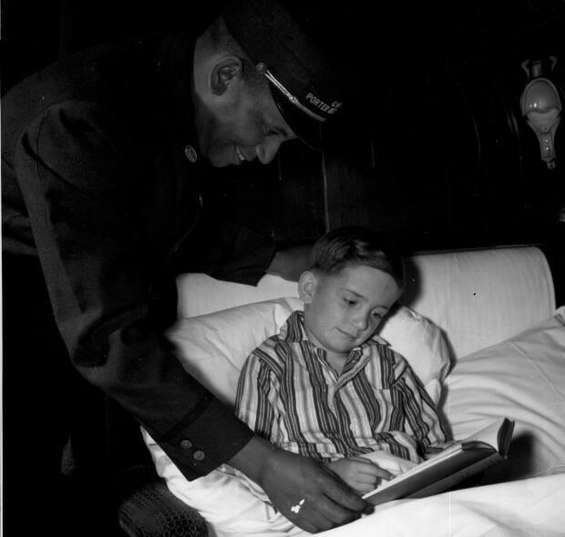 A CN porter checks on a child in a sleeping car in 1947.