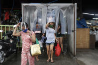 Women exit from a disinfecting area after buying food at a public market in preparation for stricter lockdown measures in Quezon city, Philippines on Monday, Aug. 3, 2020. Philippine President Rodrigo Duterte is reimposing a moderate lockdown in the capital and outlying provinces after medical groups appealed for the move as coronavirus infections surge alarmingly. (AP Photo/Aaron Favila)