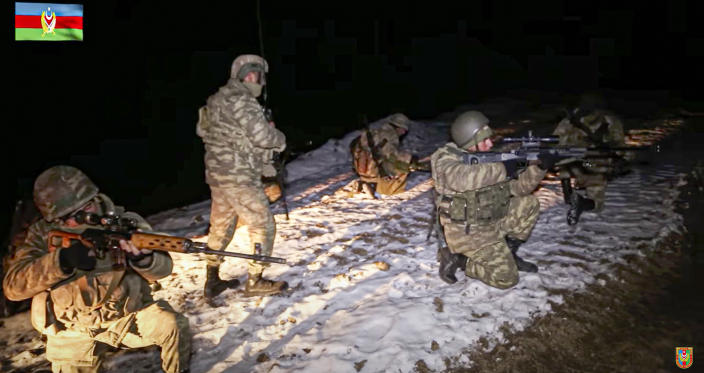 This photo taken from a video released by Azerbaijan's Defense Ministry on Wednesday, Nov. 25, 2020, shows Azerbaijan's army soldiers and a deminer looking on during a mine clearance in Kalbajar region of Azerbaijan. The Kalbajar district bordering Armenia, which houses one of the two roads linking Nagorno-Karabakh and the neighbouring country and has strategic significance for Armenians and Azeris, is due to be handed over to Azerbaijan according to a Russia-brokered cease-fire agreement between two countries in the long-running conflict over the separatist territory. (Azerbaijan's Defense Ministry via AP)