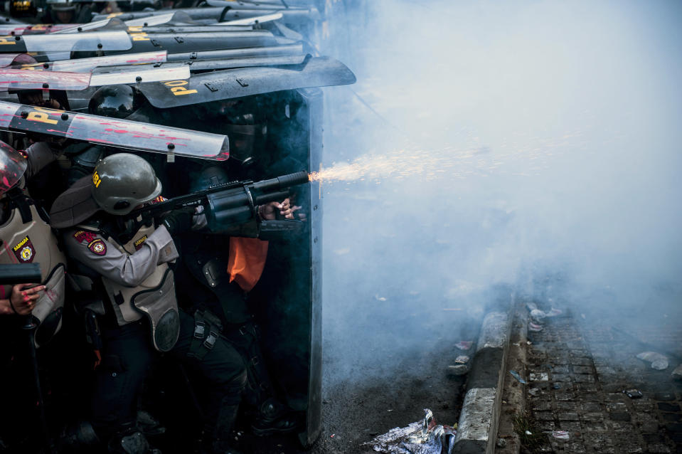 A police officer fires his tear gas launcher during a clash with student protesters in Bandung, West Java, Indonesia, Monday, Sept. 30, 2019. Thousands of Indonesian students resumed protests in several cities on Monday against a new law they say has crippled the country's anti-corruption agency, with some clashing with police. (AP Photo/Kusumadireza)