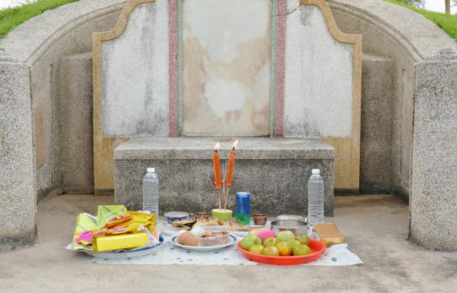 Chinese tombstone and offerings.
