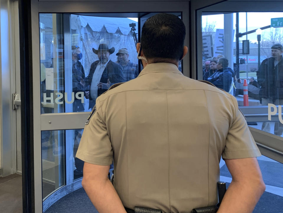 Anti-government activist Ammon Bundy, wearing a cowboy hat, yells through the closed Ada County Courthouse door at law enforcement officers inside Monday, March 15, 2021, in Boise, Idaho. Bundy was scheduled to stand trial Monday on charges that he trespassed and obstructed officers at the Idaho Statehouse during a special legislative session last fall, but Magistrate Judge David Manweiler issued a warrant for Bundy's arrest after Bundy failed to appear in the courtroom. People are required to wear face coverings while at the courthouse because of the coronavirus pandemic, but Bundy and several others were protesting the mask requirement. (AP Photo/Rebecca Boone)