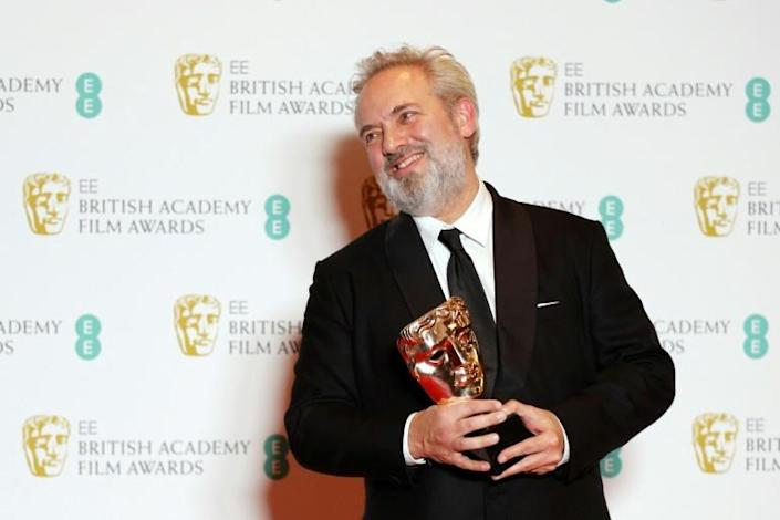 """British filmmaker Sam Mendes is leading the charge into Oscars night with his war epic """"1917"""" -- he is seen here with his Bafta award for best director (AFP Photo/Adrian DENNIS)"""