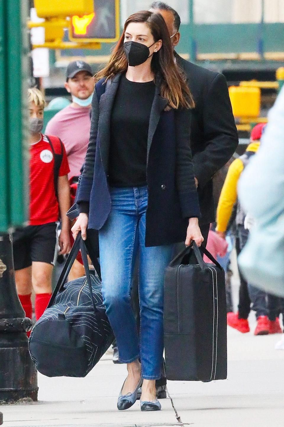 <p>Anne Hathaway carries luggage to her car as husband Adam Shulman waits to driver her on Sunday in N.Y.C.</p>