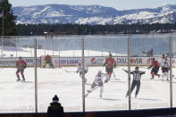 CORRECTS STATE TO NEVADA-Members of the Colorado Avalanche, in white, and the Vegas Golden Knights, red play during the first period of the Outdoor Lake Tahoe NHL hockey game in Stateline, Nev., Saturday, Feb. 20, 2021. (AP Photo/Rich Pedroncelli))