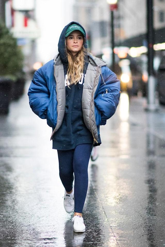 <p>Miroslava Duma is one of the most photographed street-style stars, and proves that you don't need to dress to the nines to look chic. If you prefer to be more casual, this look is all about the layers: puffer coat, hoodie, leggings, sneakers, and baseball cap. (Photo: Getty Images) </p>