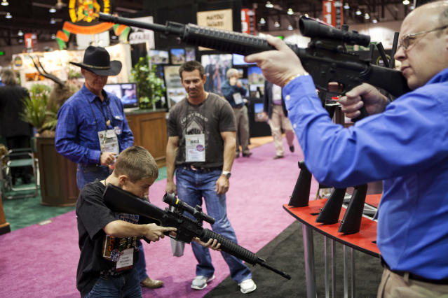 Eleven-year-old Harrison Atwood (L) and Tony Miele (R) test Trijicon rifle scopes at the Safari Club International Convention in Reno, Nevada January 29, 2011. U.S. President Barack Obama is expected to address gun control soon, in the wake of the Tucson shootings, local media reported. REUTERS/Max Whittaker (UNITED STATES - Tags: POLITICS SOCIETY) FOR BEST QUALITY AVAILABLE: ALSO SEE GM1E73B0CC801