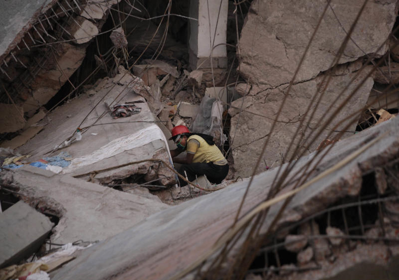 FILE - In this April 27, 2013 file photo, a Bangladeshi rescue worker searches alone in a building that collapsed Wednesday, April 24, 2013, in Savar, near Dhaka, Bangladesh. The owner of the building, who ignored inspectors who advised to close the structure when cracks appeared in the building a day before the collapse, sits at the nexus of party politics and the powerful $20 billion garment industry that drives the economy of this deeply impoverished nation. Experts say this intersection of politics and business, combined with a minimum wage of $9.50 a week that has made Bangladesh the go-to nation for many of the world's largest clothing brands, has created a predictable danger for factory workers. Government officials, labor activists, manufacturers and retailers all called for improved safety standards after a November fire in the same suburb, when locked emergency exits trapped hundreds of garment workers inside amid spreading flames and 112 people died. But almost nothing has changed. (AP Photo/Kevin Frayer, File)