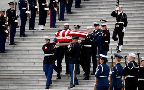 The flag-draped casket of former President George HW Bush is carried by a joint services military honour guard - Credit: AP