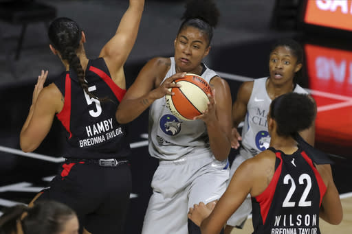 Minnesota Lynx's Damiris Dantas, center, grabs a rebound between Las Vegas Aces' Dearica Hamby (5) and A'ja Wilson (22) during the first half of a WNBA basketball game Thursday, Aug. 13, 2020, in Bradenton, Fla. (AP Photo/Mike Carlson)