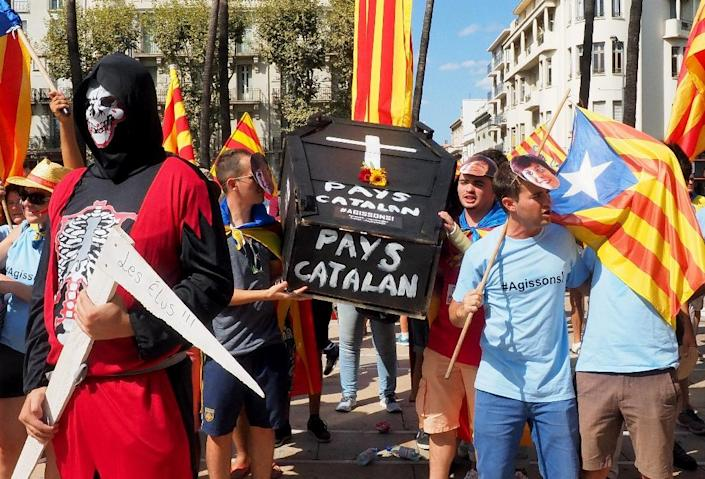 Participants march with a mock-up of a coffin bearing the lettering 'Catalan country' during a demonstration in Perpignan, southern France, on September 10, 2016 (AFP Photo/Raymond Roig)