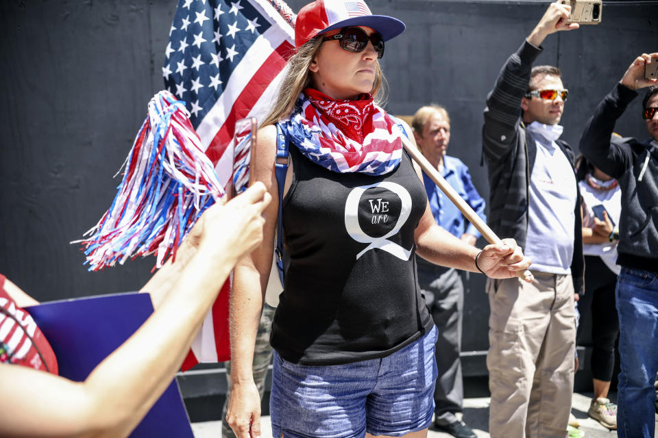 Conspiracy theorist QAnon demonstrators protest during a rally to re-open California and against Stay-At-Home directives on May 1, 2020 in San Diego, California. - Rallies have been held at several state capitols across the country as protesters express their deep frustration with the stay-at-home orders that are meant to stem the spread of the novel coronavirus. (Photo by Sandy Huffaker / AFP) (Photo by SANDY HUFFAKER/AFP via Getty Images)