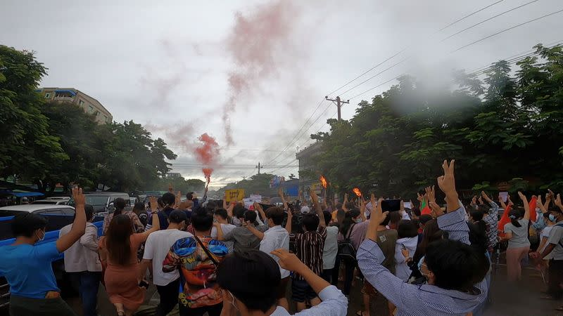 Demonstrators march on a street during a protest in Yangon