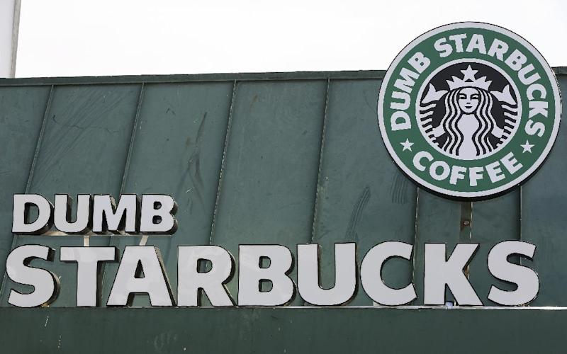 "The sign at Dumb Starbucks coffee in Los Angeles, is displayed Monday, Feb. 10, 2014. The store resembles a Starbucks with a green awning and mermaid logo, but with the word ""Dumb"" attached above the Starbucks sign. Spokeswoman Laurel Harper says the store is not affiliated with Starbucks and, despite the humor, the store cannot use the Starbucks name. (AP Photo/Damian Dovarganes)"